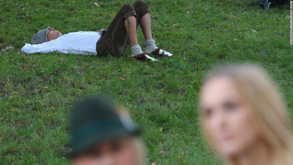 "A man rests on a patch of grass on the first day of the festival. <a href=""http://www.cnn.com/2013/09/20/travel/oktoberfest-2013-9-rules/index.html"">Here are 9 rules for surviving Oktoberfest.</a>"