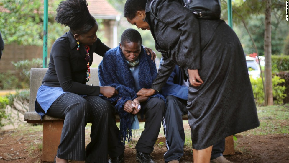 Stephen, center, is comforted by relatives as he waits for the post mortem exam of his father, who was killed in Saturday's attack at the mall.