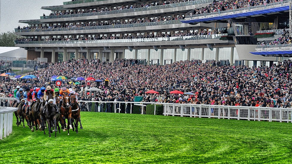 <strong>Royal Ascot, Ascot, Berkshire, UK:</strong> A packed grandstand watches a tightly-bunched group of runners during a race at Royal Ascot in June.