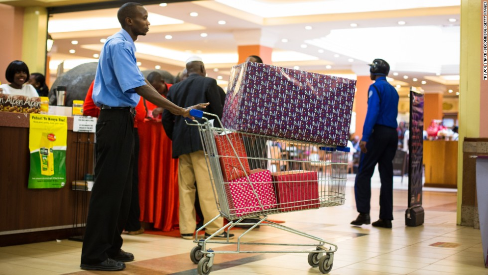 An employee pushes a shopping cart filled with gift-wrapped products inside the mall.