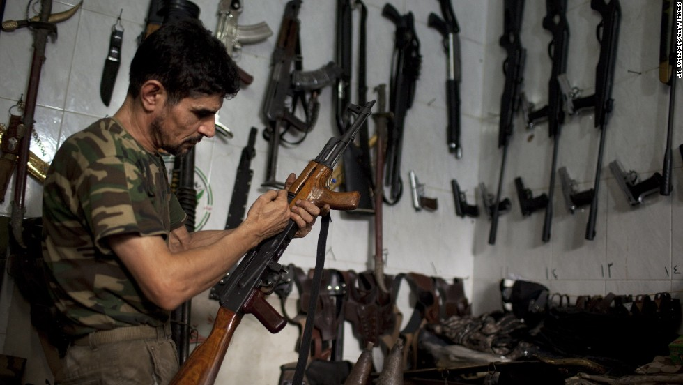 A man checks an AK-47 at his gun shop in Aleppo, Syria, on Saturday, September 21.