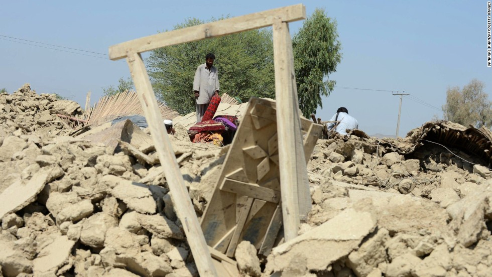 Survivors gather around destroyed houses in the Awaran district on September 25.