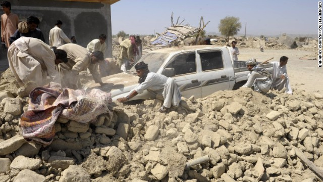 People clear debris off of a truck in Awaran on September 25.