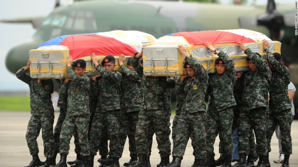 Soldiers carry the flag-draped coffin of policemen who died at the Zamboanga rebel attack in Mindanao. The coffins arrive at Villamor airbase in Manila on September 25. Fighting between rebels and soldiers in the city has entered its third week.