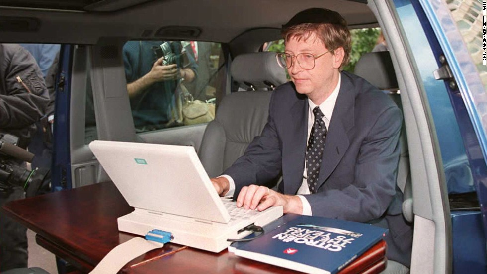 Gates demonstrates Microsoft's Windows 95 program from his automobile before a press conference in Paris in September 1994.