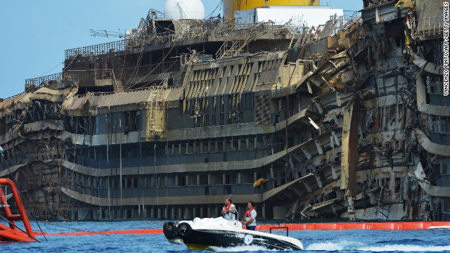 Members of the US salvage company Titan and Italian firm Micoperi pass by the destroyed side of the wreckage of Italy's Costa Concordia cruise ship which begins to emerge from water near the harbour of Giglio Porto. Salvage operators in Italy lifted the Costa Concordia cruise ship upright from its watery grave off the island of Giglio in the biggest ever project of its kind. The ship's horn sounded for the first time since the January 13, 2012 tragedy, its sound