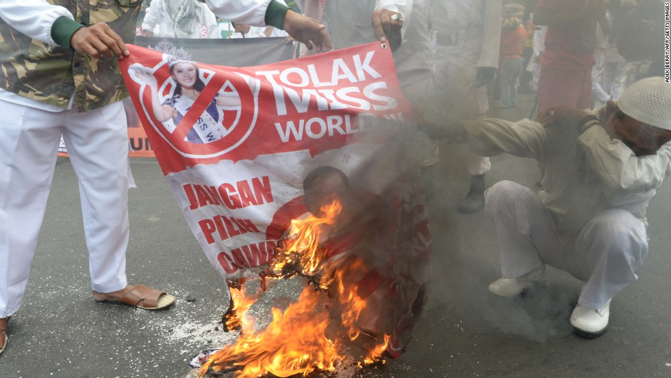 "Protesters burn a banner featuring Miss World 2012 Yu Wenxia from China reading ""Reject Miss World"" during a protest in Jakarta on September 3."