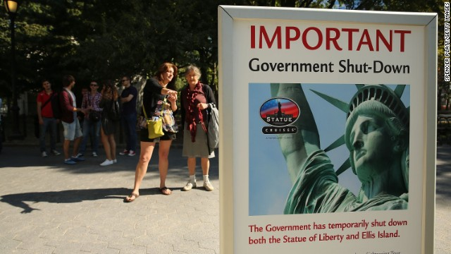 People look at a sign advertising the closure of the Statue of Liberty because of the government shutdown.