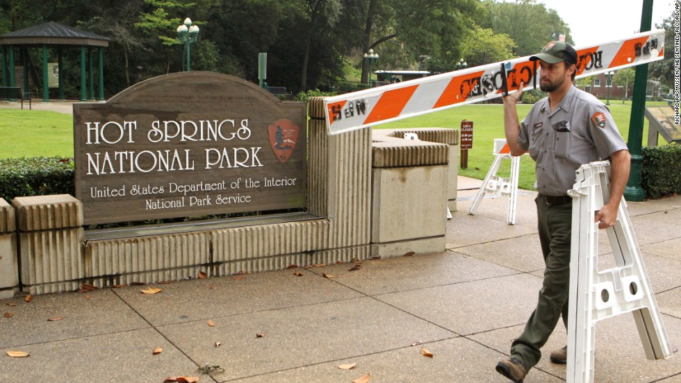 Hot Springs National Park employee Stacy Jackson carries a barricade while closing Arlington Lawn in Hot Springs National Park in Arkansas on October 1.