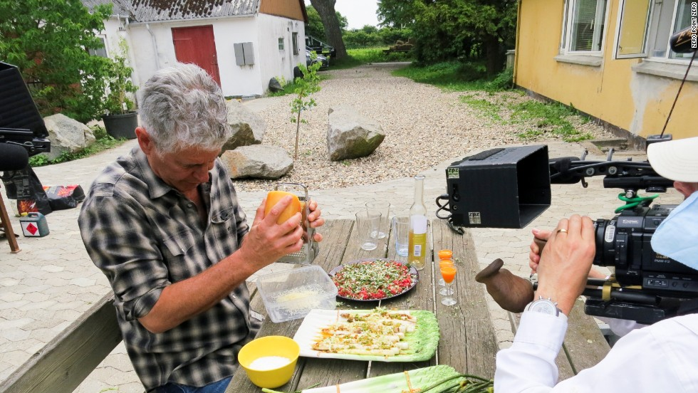 Bourdain grates cheese on a feast that came directly from Wiuff's farm.