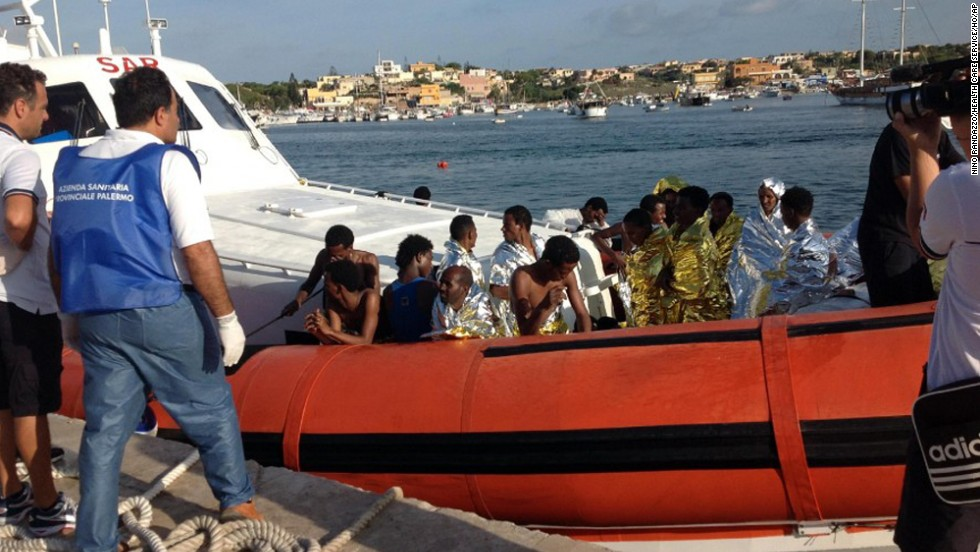 An Italian Coast Guard boat carries rescued migrants into the port of Lampedusa on Thursday, October 3. According to the nation's coast guard, a boat carrying as many as 500 people capsized and caught fire off the Italian island of Lampedusa.