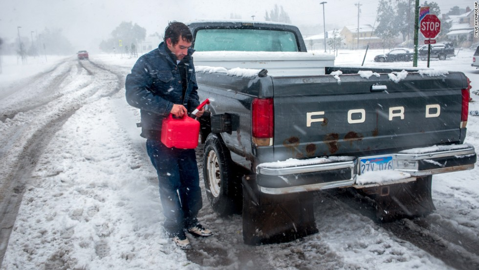 Ronnie Tonuci, 21, puts gas in his truck after it ran out in the middle of an early season blizzard on October 4, in Rapid City, South Dakota.