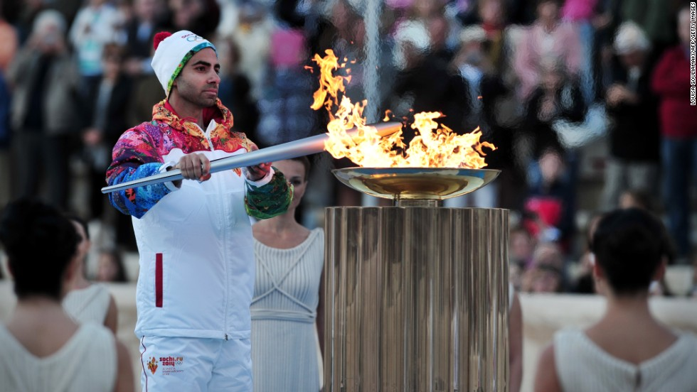 The last torchbearer of the Greek leg, figure skater Panagiotis Markouizos, lights the cauldron at the Panathenaic stadium to end a week-long journey.