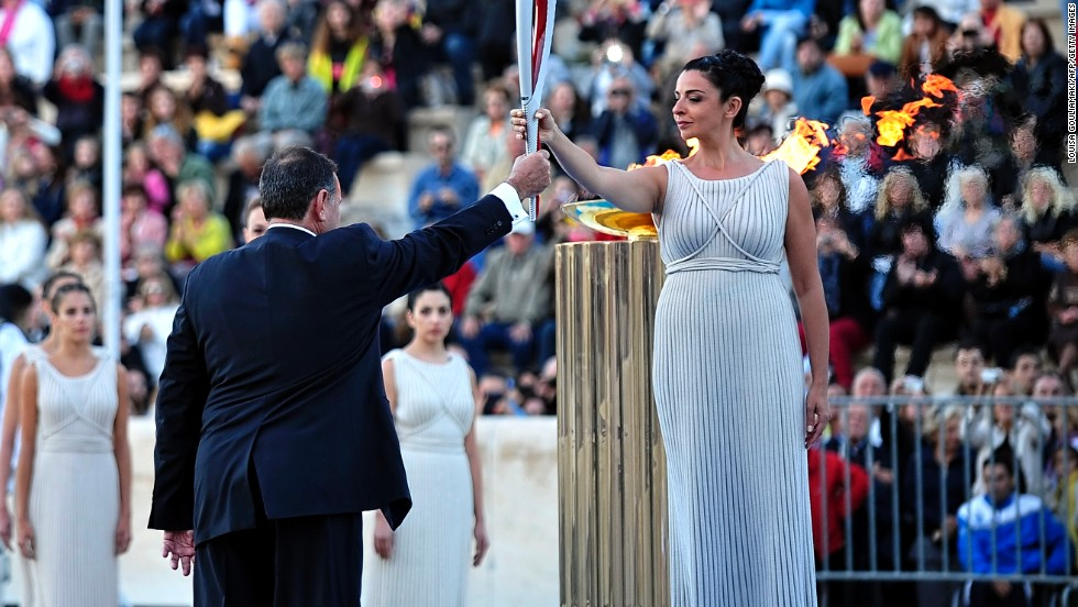 Actress Ino Menegaki, playing a high priestess, hands the Olympic flame to the president of the Hellenic Olympic Committee, Spyros Kapralos, at the Panathenaic stadium in Athens.