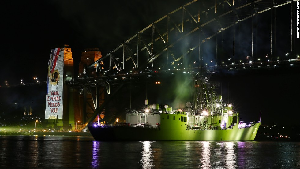 The HMAS Sydney steams underneath the Sydney Harbor Bridge on October 5 as fireworks color the night.