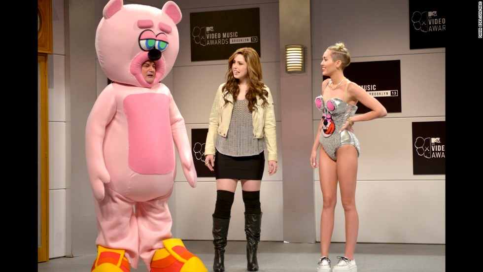 "Bobby Moynihan, left to right, Vanessa Bayer and Cyrus perform a skit on ""Saturday Night Live"" on October 5, in which they mock Cyrus' VMA performance."