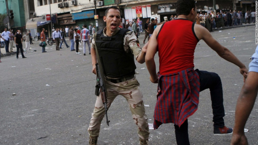 An Egyptian army officer tries to prevent a supporter of Defense Minister Gen. Abdel-Fattah al-Sisi from clashing with Morsy backers on October 6 in Cairo.