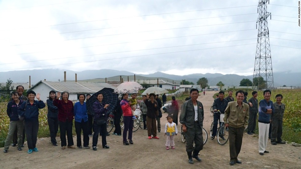 Peasants and villagers standing by the road to look at the Western cyclists