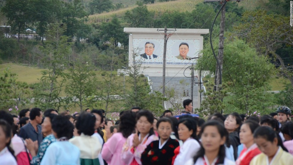 "Spectators waiting for the bikers to reach the finish line. In the background the ""Great"" and ""Dear Leaders"" Kim Il Sung and his son, Kim Jong-Il."