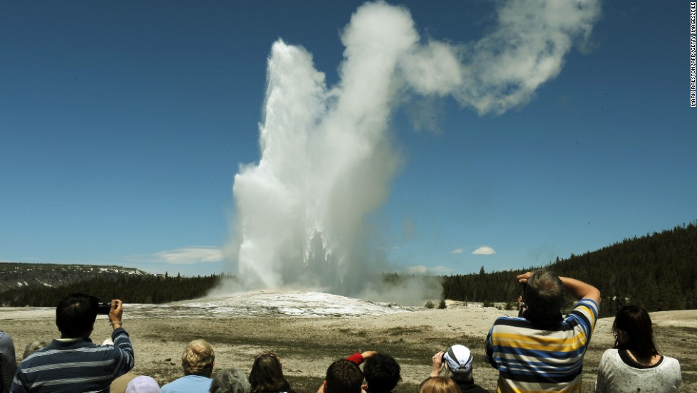 "Tourists watch the Old Faithful geyser in the Yellowstone National Park in Wyoming in June 2011. One tourist told a Massachusetts newspaper that National Park Service guards treated members of her tour group brusquely and told them not to ""recreate"" while taking pictures of bison."
