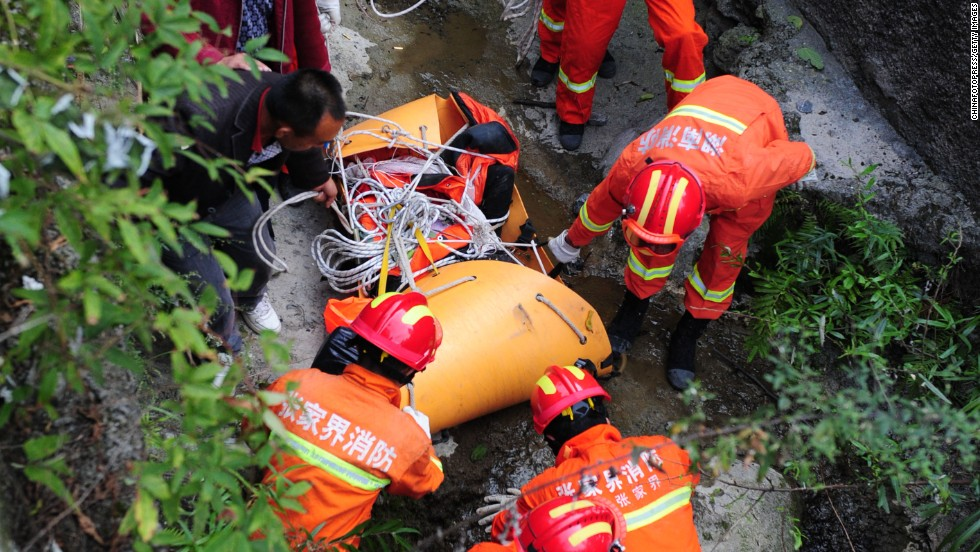 Rescuers carry Kovats' body down a steep path in Tianmen Mountain National Forest Park on October 9. Kovats jumped at 2:51 p.m. local time, according to news agency Xinhua.