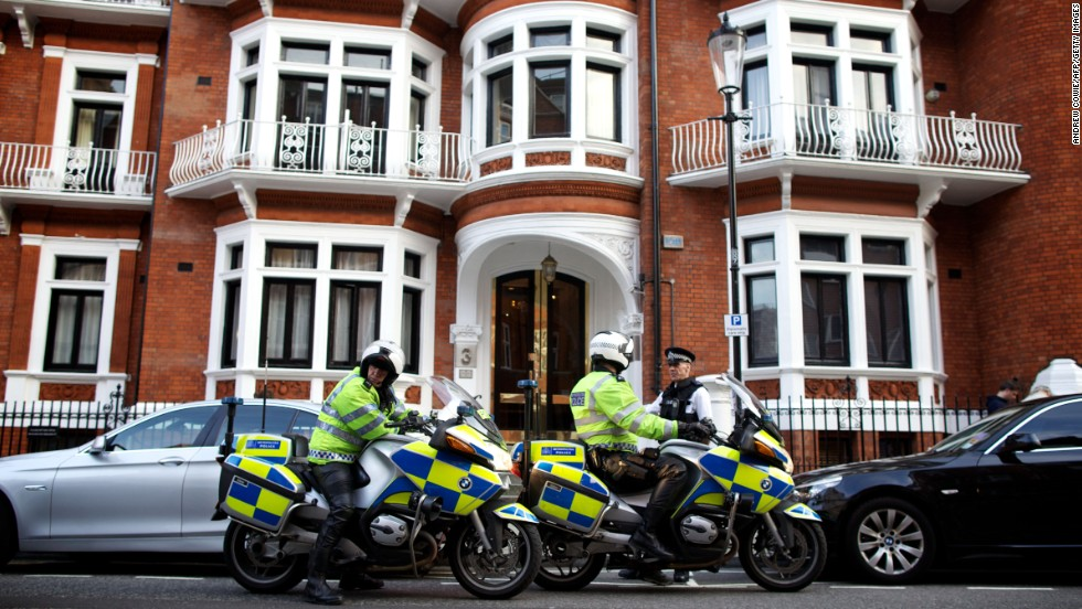 Two police officers stand guard outside the Ecuadorian Embassy in London on June 20, 2012, after Assange took refuge there to avoid arrest and extradition by British police. Ecuador granted him asylum in August 2012.