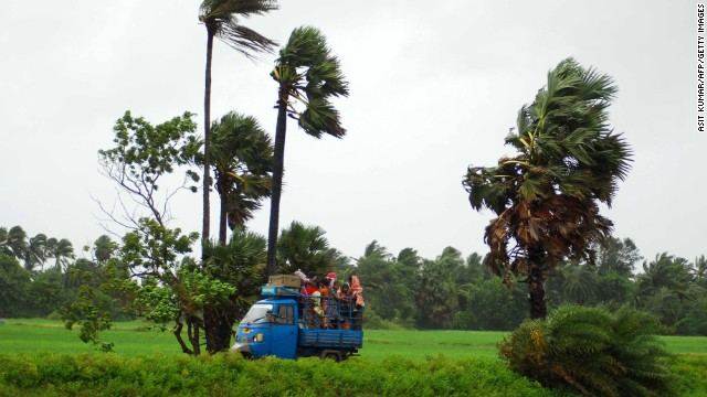 Indian evacuees travel in an auto rickshaw as they leave their village towards a safe place through heavy wind and rain in Sanabandha Village near Gopalpur, about 195 south from eastern city Bhubaneswar on October 12, 2013.   Nearly half a million people have been evacuated from India's impoverished east coast ahead of a massive cyclone expected to make landfall on October 12 evening, disaster officials said.  AFP PHOTO/ASIT KUMAR        (Photo credit should read ASIT KUMAR/AFP/Getty Images)