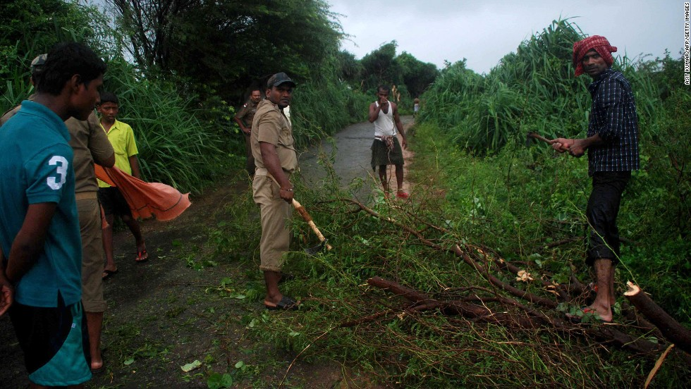 Volunteers clear branches off the road in the village of Badabandha on October 12.