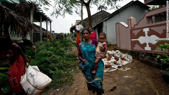 An Indian woman carries her child as they leave their home at Donkuru village, in the Srikakulam district on October 12, 2013.   Nearly half a million people have been evacuated from India's impoverished east coast ahead of a massive cyclone expected to make landfall on October 12  evening, disaster officials said.  AFP PHOTO/ MANAN VATSYAYANA        (Photo credit should read MANAN VATSYAYANA/AFP/Getty Images)