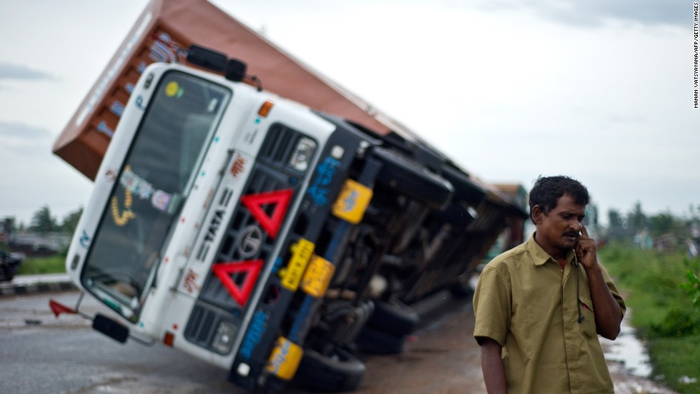 Indian truck driver Jairam Yadav speaks on his mobile phone after his truck carrying Toyotas was overturned by strong wind on the highway linking Andhra Pradesh and Odisha, India, on October 13.