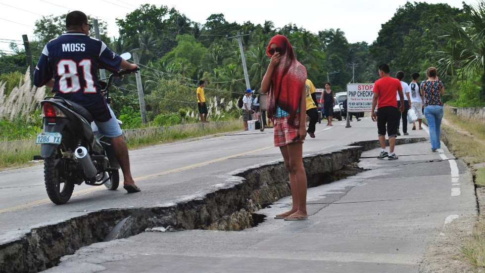People walk along a damaged road in the province of Bohol on Tuesday, October 15.