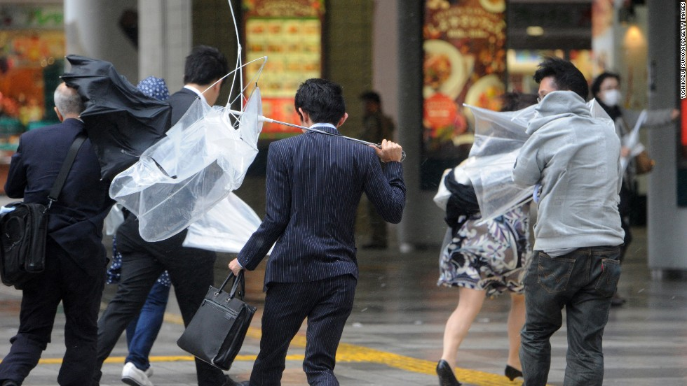 People in Tokyo rush to avoid heavy rainfall and strong winds.