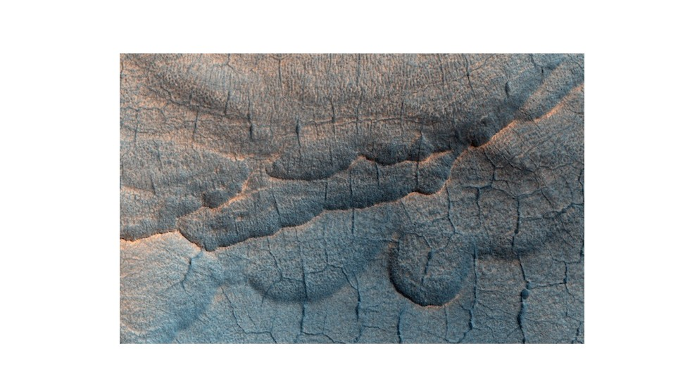 "Water is thought to exist in large deposits beneath the Martian surface. When it disappears, the ground sinks and creates scallop-shaped depressions and polygonal troughs. The formations are known as ""<a href=""http://hirise.lpl.arizona.edu/ESP_032108_2240"" target=""_blank"">thermokarsts</a>,"" a variety of which can be seen here."