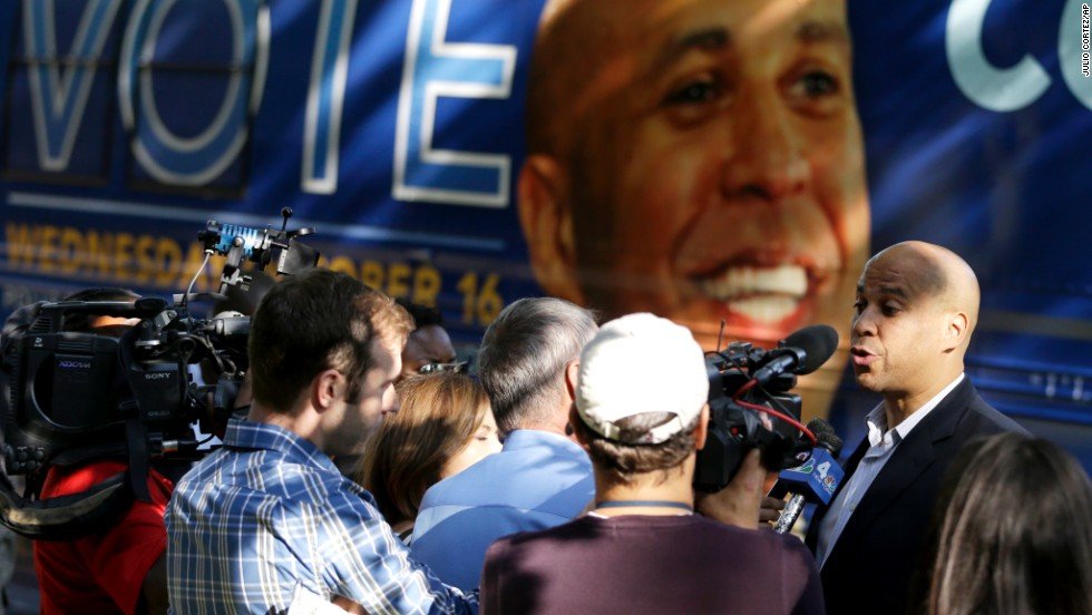 Booker talks to reporters near his tour bus while visiting supporters at a Newark senior center on October 15.