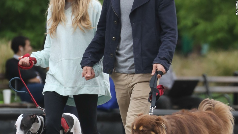 Amanda Seyfried and Justin Long hold hands as they walk their dogs on October 17.