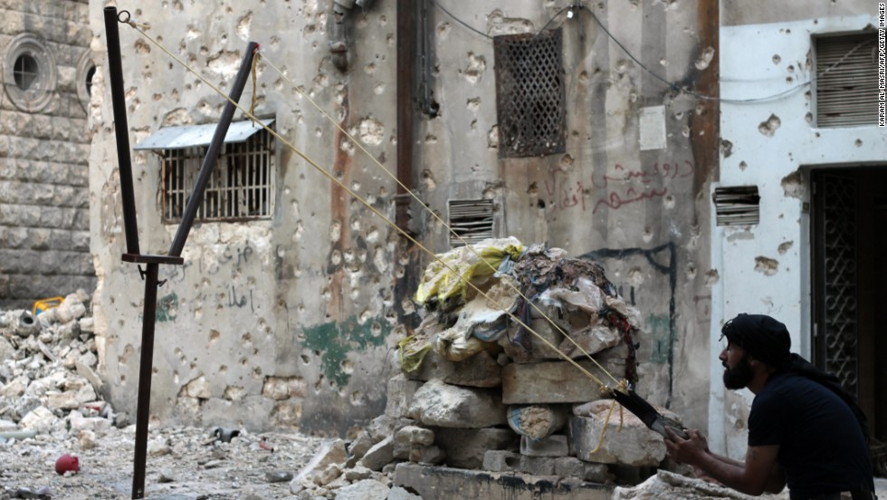 A Syrian opposition fighter aims a catapult toward regime forces in Aleppo, Syria, on Thursday, October 17.