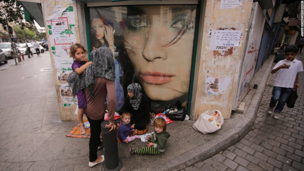 A Syrian refugee begs with her children on a street in Beirut, Lebanon, on Friday, October 18.