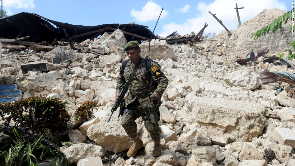 A Philippine soldier walks through the ruins of the historic Holy Cross Parish Church in Maribojoc on October 18.