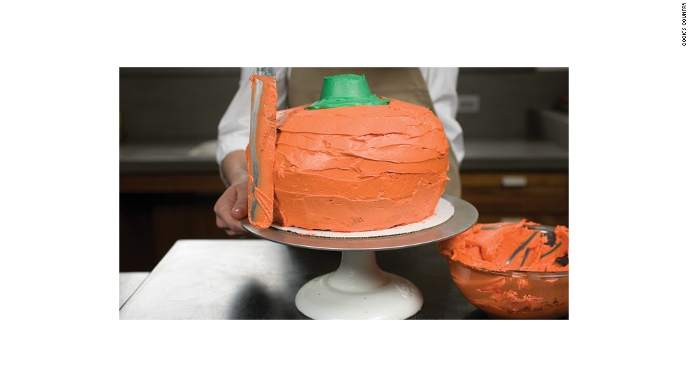 "Using a cake spatula, cover the entire cake with orange frosting. <a href=""http://eatocracy.cnn.com/2013/10/24/pumpkin-cake/"">See the full recipe.</a>"