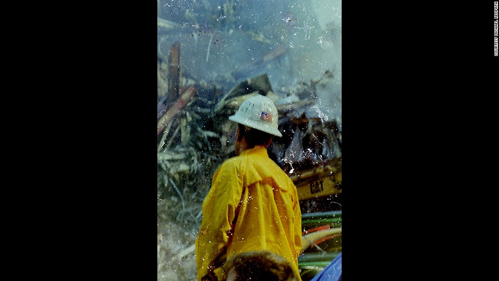 A firefighter stands before the World Trade Center rubble at ground zero. The image has scratches and water damage that give it a smoky, three-dimensional feel.