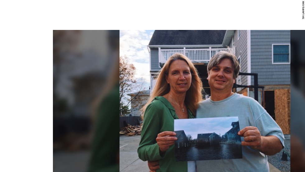 Darren and Anne Erbe stand in front of their new home, holding a photo of their old house in Bay Head, New Jersey, which was taken after Hurricane Sandy hit on Oct. 29, 2012. They had to move four times in the past year.