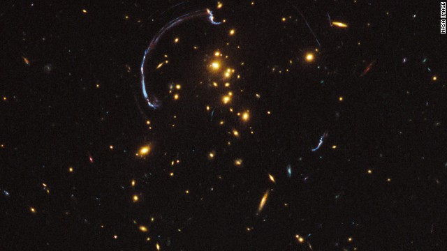 Galaxies act as a lens to stretch images of more distant galaxies, the blue arcs that are evidence of dark matter.