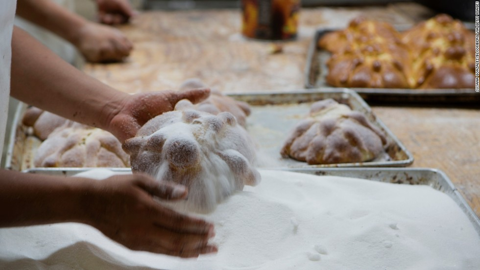 A baker adds sugar to loaves of pan de muerto at La Ideal bakery in Mexico City on Thursday, October 24. The pan de muerto, or bread of the dead, is a sweet soft bread shaped like a bun often decorated with bone-like pieces traditionally baked in Mexico during the weeks leading up to Dia de los Muertos.