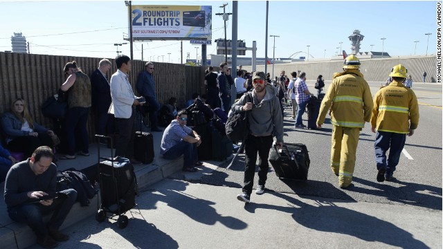 Caption: epa03932798 Passengers wait on the curb after being evacuated from Los Angeles International Airport after a suspected shooter opened fire in Terminal Three at Los Angeles, California, USA 01 November 2013. First reports indicated at least four people have been shot including the shooter. EPA/MICHAEL NELSON /LANDOV   Photographers/Source: MICHAEL NELSON/EPA /LANDOV..