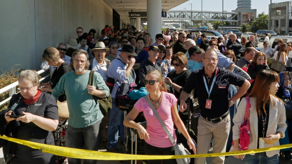 Passengers evacuated from Terminal 1 wait outside the airport.