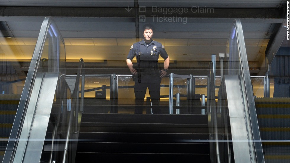 A Los Angeles Airport Police officer stands in front of Terminal 3 security screeners after law enforcement officials completed their investigation and prepare to reopen the terminal at LAX on November 2.