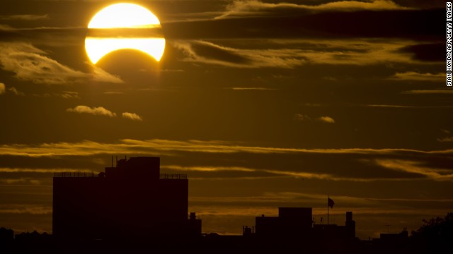 A partial Solar eclipse is seen just after sunrise over the Queens borough of New York across the East River on November 3, 2013 in New York.    AFP PHOTO/Stan HONDA        (Photo credit should read STAN HONDA/AFP/Getty Images)