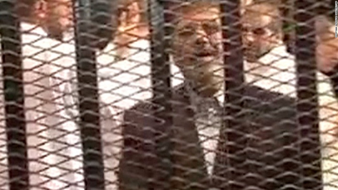 "This image, made from video provided by Egypt's Interior Ministry, shows Morsy speaking from the defendant's cage as he stands with co-defendants during his hearing. ""I am Dr. Mohamed Morsy, the President of the republic,"" Morsy said. ""The coup is a crime and ... treason."""