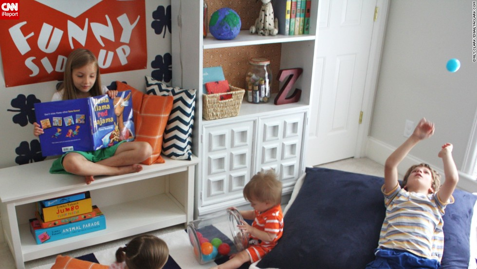 "<a href=""http://www.emilyaclark.com/"" target=""_blank"">Clark</a> decorated this bright space with orange accents to be kid friendly. ""I wanted it to be a spot that all five of our children could use for reading, playing or just hanging out.""<br /> <br />"