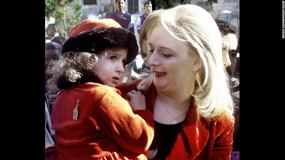 Arafat's wife, Suha, carries their daughter, Zahwa, in the West Bank town of Bethlehem on December 15, 1998.